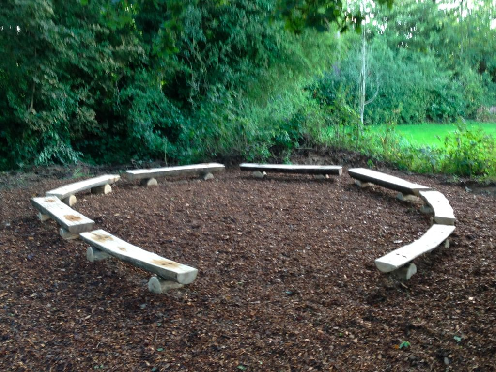seating-rustic-split-log-benches-bench-by-the-wild-deck-company-arranged-in-a-circle-in-woodland