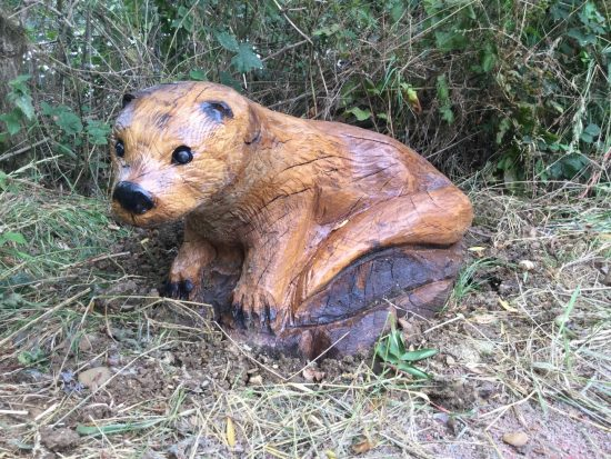 otter carving on ground